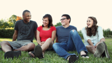 group of people sitting on grass and smiling