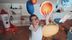 child playing with solar system toy inside