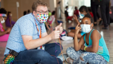 counselor in mask helping a child at camp