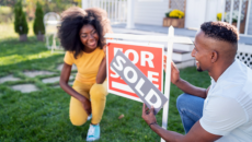 Couple putting sold sign on their new home