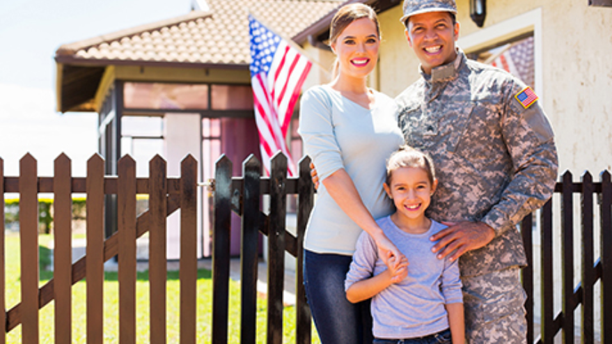 Veteran family standing in front of home