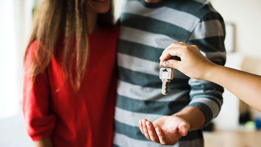 couple holding keys for new home