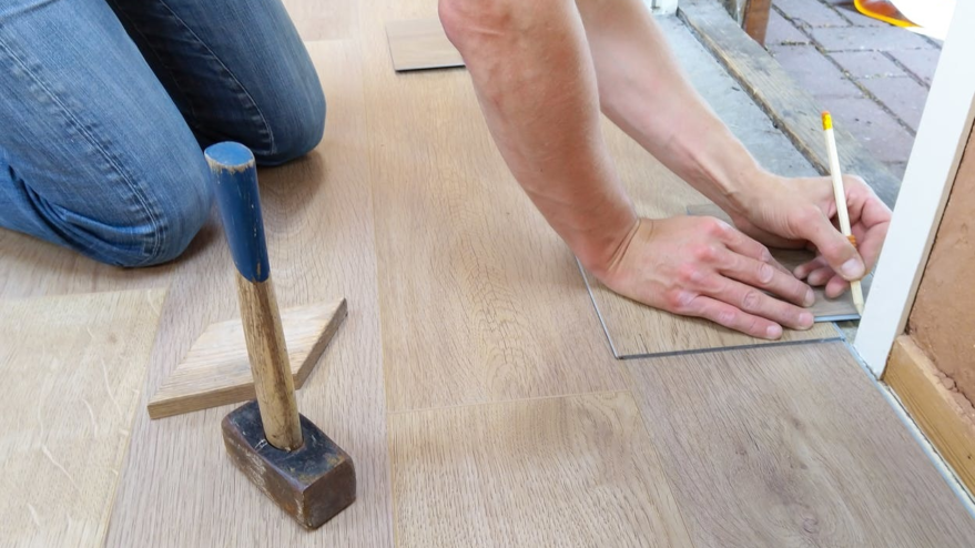 man doing work on floor with hammer