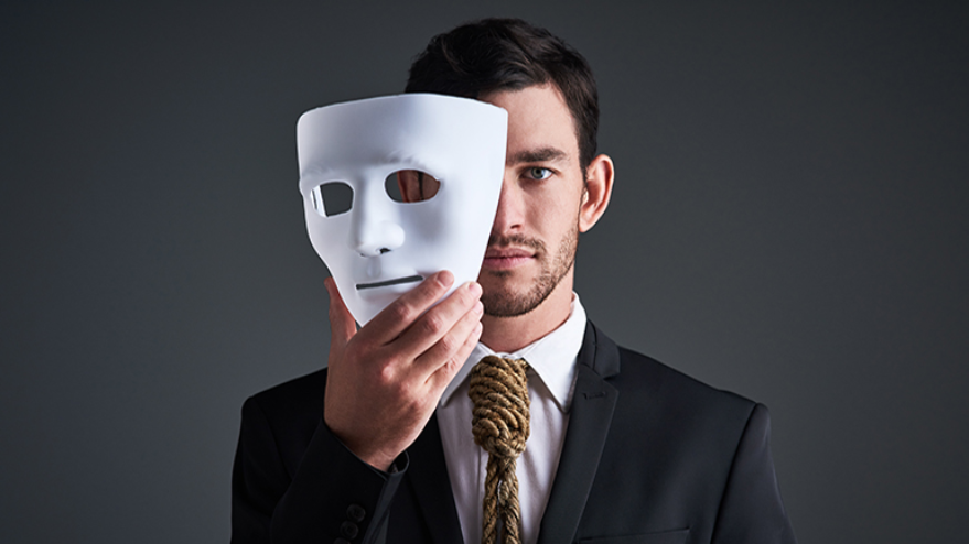 man in suit holding white mask over his face