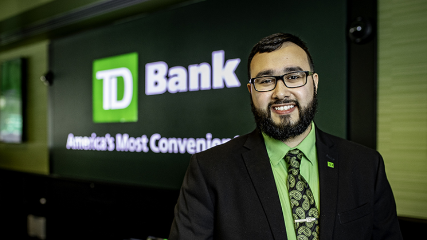 Man standing in store in front of TD sign