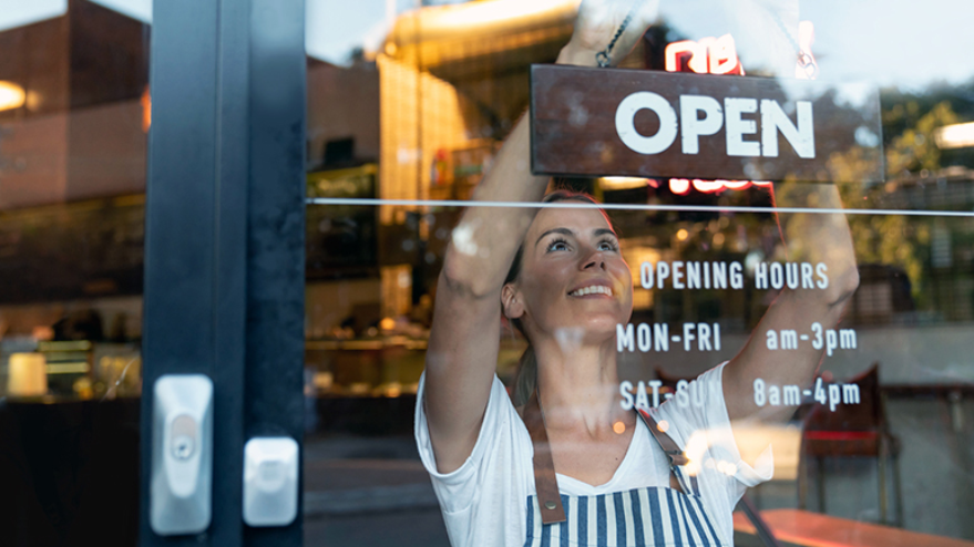 Business owner putting open sign up
