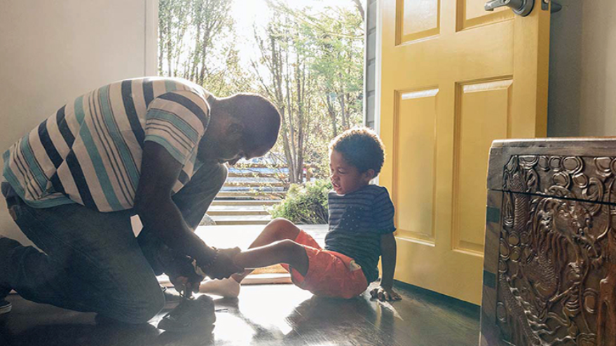 Dad tying his son's shoes