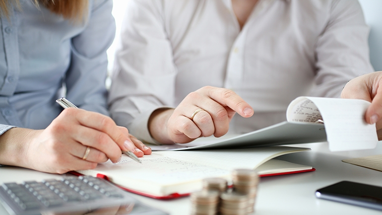 man and women sitting at table doing finances