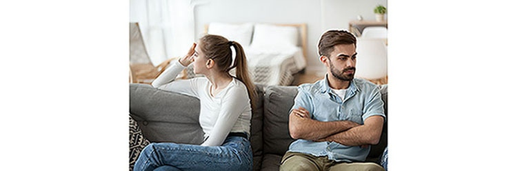 Man and woman sit separately on couch