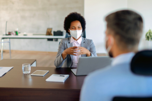 woman with facemask speaking to male coworker